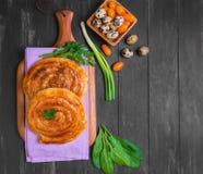 Spiral filo pie. S burek, Greek Bougatsa, lettuce, green onions, parsley, yellow cherry tomatoes, quail eggs in a wooden bowl on a napkin on a dark black Royalty Free Stock Images