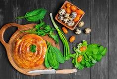Spiral filo pie. S burek, Greek Bougatsa, lettuce, green onions, parsley, yellow cherry tomatoes, quail eggs in wooden bowl on napkin, dark black background Stock Photo