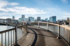 Spiral fot- bro som förbiser den Willamette floden och den i stadens centrum stadshorisonten i Portland, Oregon December 2017 Royaltyfri Bild
