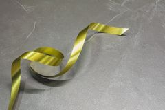 The spiral golden ribbon on leather table. Stock Image