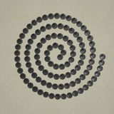 Spiral of grey stone on sand Stock Photos