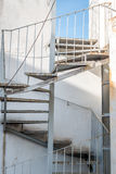 Spiral industrail metal stairs and a building Royalty Free Stock Photo