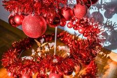 Spiral julgran f?r modern metall som dekoreras med r?da skinande bollar royaltyfri foto