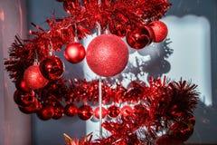 Spiral julgran f?r modern metall som dekoreras med r?da skinande bollar arkivfoton