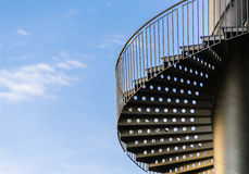 Spiral ladder to the blue sky. Twist staircase on a background of blue sky Stock Photo