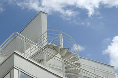 Spiral metal stairs on top of a building. View to roof of a modern building with terraces connected with a spiral staircase Royalty Free Stock Photos
