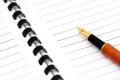 Spiral note pad with fountain pen. Fountain pen on a blank spiral note pad Royalty Free Stock Photo