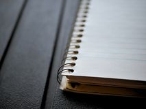 Blank spiral note pad, paper on rugged black background. Spiral note pad, lined paper on rugged black background Royalty Free Stock Photography