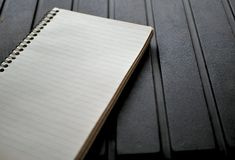 Blank spiral note pad, paper on rugged black background. Spiral note pad, lined paper on rugged black background Stock Photo