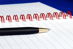 The spiral note pad with a pen. Isolated on blue Stock Image