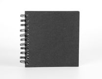 Spiral notebook with black cover on white. Stock Photo