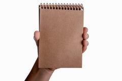 Spiral notebook in child hand. Spiral brown notebook in child hand on a white background Stock Photos