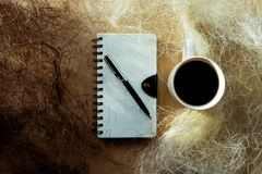Spiral Notebook and Coffee Mug. Spiral notebook, pen, mug of coffee and shredded paper Stock Photo