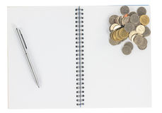 Spiral notebook with coins isolate Royalty Free Stock Photography