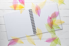 Spiral notebook with color dried leaves on white wood Stock Photography
