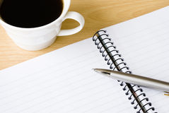 Spiral notebook with cup of coffee and ballpoint. Arranged on wooden table Stock Photos