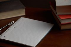Spiral notebook on desk with books royalty free stock photography