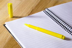 Spiral notebook with highlighter. Spiral notebook with yellow highlighter arranged on wooden background Royalty Free Stock Photos