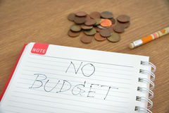 Spiral notebook is noted with no budget text and some coins on wooden table Royalty Free Stock Photo