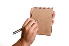 Spiral notebook and a pen. Spiral brown notebook and a pen in child hand on a white background Stock Images