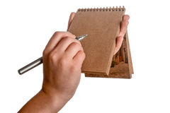 Spiral notebook and a pen. Spiral brown notebook and a pen in child hand on a white background Stock Photo