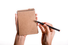 Spiral notebook with pen in child hand. Spiral brown notebook with a pen held by a child on a white background Royalty Free Stock Photography