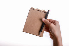 Spiral notebook with pen in child hand. Spiral brown notebook with a pen held by a child on a white background Stock Photos