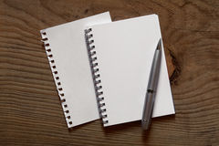 Spiral notebook and pen on wooden desk Stock Photography