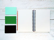 Spiral notebook with pencil and cards on a white wood background Royalty Free Stock Photography
