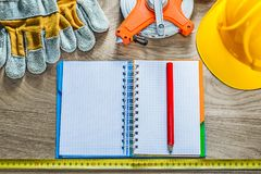 Spiral notebook pencil protective gloves measuring tape building. Helmet on wooden board Royalty Free Stock Images