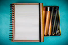 Spiral notebook and pencils. Spiral notebook in lines and different drawing pencils, blue background Stock Image