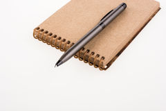 Spiral notebook and pollpoint pen. On a white background Stock Photos