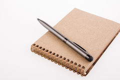 Spiral notebook and pollpoint pen. On a white background Stock Images
