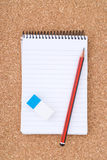 Spiral Notepad, Pencil and eraser on cork surface Stock Photos