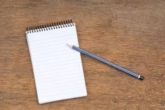 Spiral Notepad and Pencil on a wooden table Stock Image
