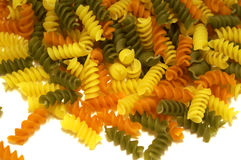 Spiral Pasta. Twisted yellow, green and orange vegetable spiral pasta stock images