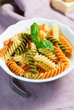 Spiral pasta and basil in bowl Stock Photos