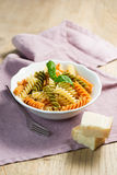 Spiral pasta and basil in bowl with cheese Royalty Free Stock Images