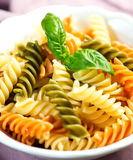 Spiral pasta in bowl with basil Royalty Free Stock Images