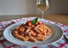Spiral pasta fusilli with tuna fish, tomato sauce,olive oil and basil. It is typical mediterranean dish which people eat especially during the summer and hot Stock Photos
