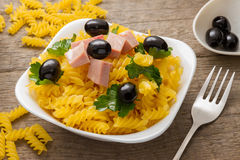 The spiral pasta with olives and parsley. Spiral pasta with olives and parsley. On the old Board. Selective focus Royalty Free Stock Photos