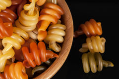 Spiral pasta trottole tricolore isolated in wooden bowl. On black background, close up Stock Images