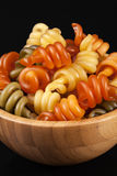 Spiral pasta trottole tricolore  in wooden bowl. On black background, close up Royalty Free Stock Photos