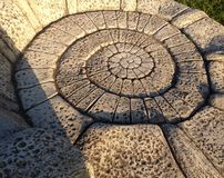 Spiral Pattern Stone Architecture. The spiral architecture of an artistic seat fashioned from stone Stock Photos