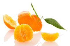 Spiral peel of orange mandarin with green leafs and a slice of c Royalty Free Stock Photo