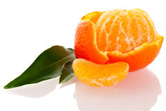 Spiral peel of orange mandarin with green leafs and a slice of c Stock Photos