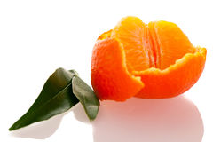 Spiral peel of orange mandarin with green leafs and a slice of c Stock Photo