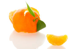 Spiral peel of orange mandarin with green leafs and a slice Royalty Free Stock Photography