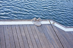 Spiral rope. A folded spiral mooring rope with a end knot around a cleat on a wooden pier Royalty Free Stock Photography