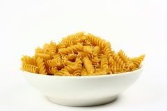 Spiral Rotini Pasta In White Bowl. A white bowled filled with uncooked rotini pasta photographed on a white background Stock Images